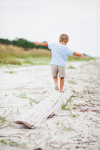 Boy balancing on a piece of driftwood on the beach.