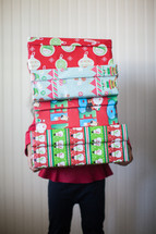 boy child holding stacked Christmas gifts