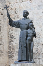 Statue of a priest holding a cross with his arm around a boy.