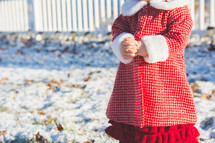A toddler stands in the snow in winter wearing a red coat