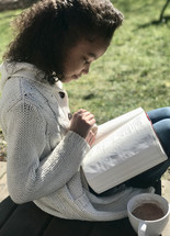 a girl reading a Bible outdoors