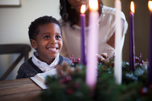 mother and son lighting an Advent wreath and reading a Bible