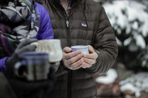 people with mugs standing outdoors in snow