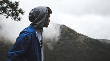 man in a hoodie looking out at a mountain