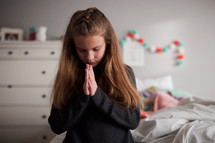 a girl praying bedside
