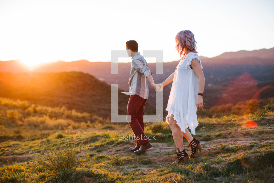 a couple walking holding hands on a mountaintop at sunset