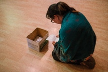 a woman placing her sins in a box during a worship service