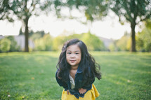 A little girl with long dark hair in a field of grass.