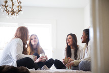 young women sitting on a bed talking