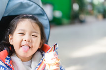 toddler girl eating ice cream in a stroller