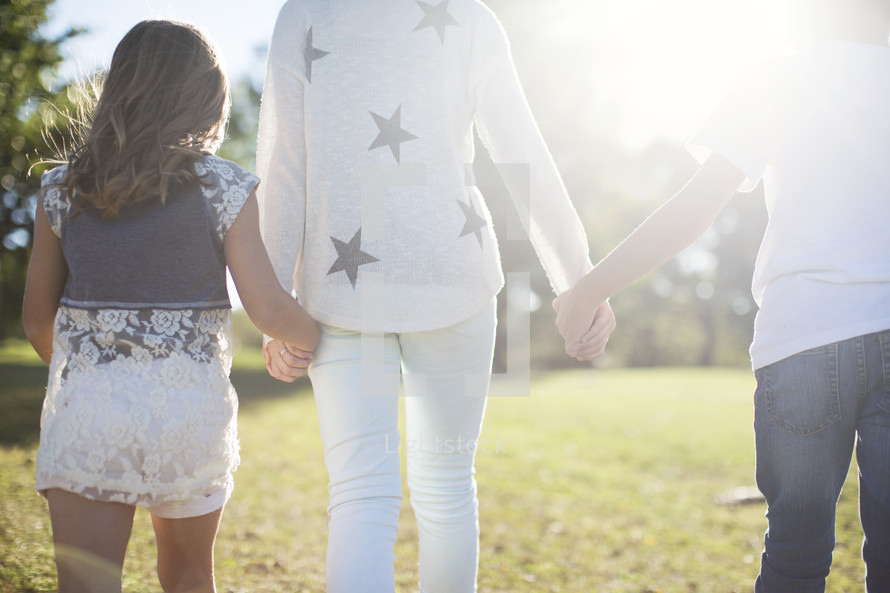 siblings walking holding hands in the grass