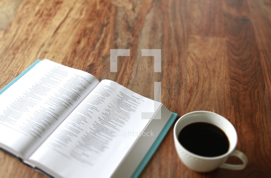 Open Bible and a white cup of coffee on a wood table