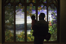 a father holding his toddler looking at a stained glass window