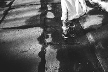 a child in snow boots standing on a sidewalk