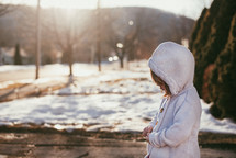 a child in a coat standing on a sidewalk in winter