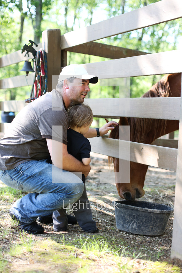 father and son petting a horse