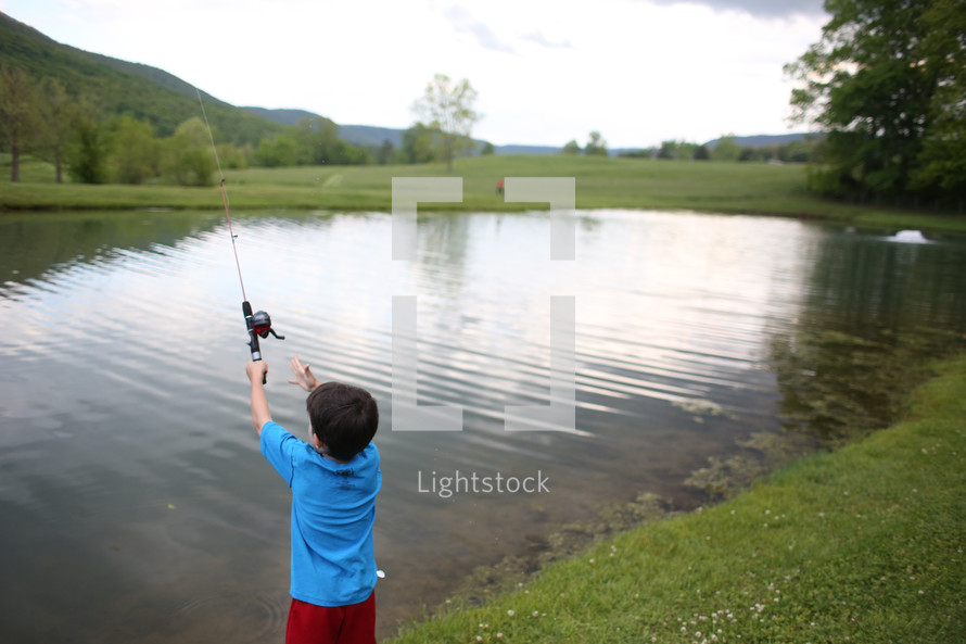 a boy child fishing at a pond
