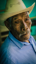An elderly Hispanic man in a cowboy hat.