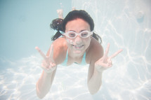 a teen girl under water with goggles