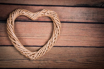 A heart shaped wreath on a wooden table.