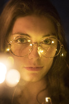 face of a young woman with bokeh lights