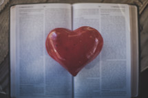 A red heart on the pages of an open Bible