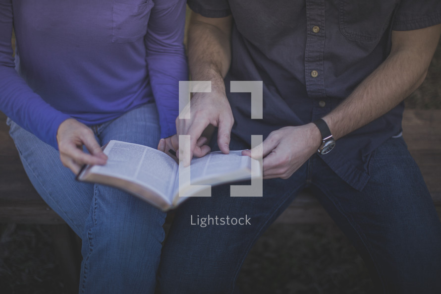 A man and woman sitting on a bench reading the Bible together