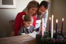 family reading a Bible near an Advent wreath
