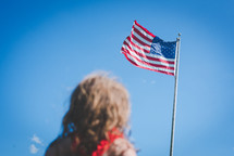 girl looking up at an American flag on a flagpole