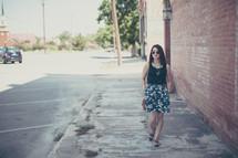 a woman with a purse walking down a sidewalk alone