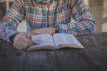 A man sitting at a table reading the Bible
