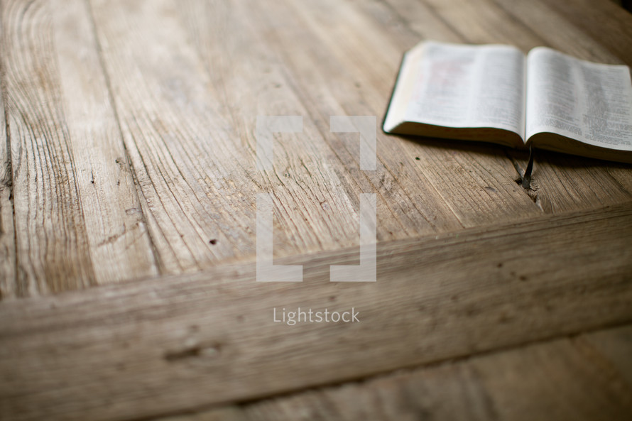 open Bible lying on a wood table