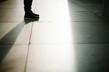 feet standing in sunlight on a marble floor