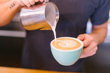 man pouring cream in coffee