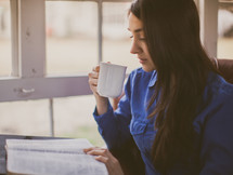A woman drinking coffee while reading a Bible