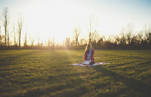 teen girl sitting on a blanket in the grass holding a Bible