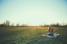 teen girl sitting on a blanket in the grass reading a Bible