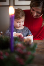 mother and daughter reading a Bible in front of an Advent wreath
