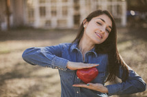 A smiling young woman holding a red heart