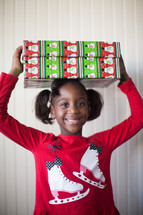 a girl child holding a wrapped Christmas gift over her head