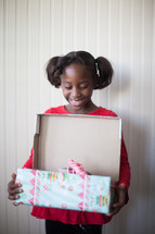 a girl child opening a Christmas present
