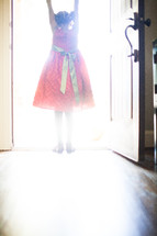 a little girl in a red dress standing in the light from an open doorway