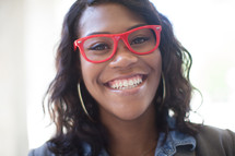 a smiling young woman in red reading glasses