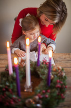 mother and daughter reading a Bible near an Advent wreath