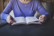 A woman sitting at a table reading the Bible