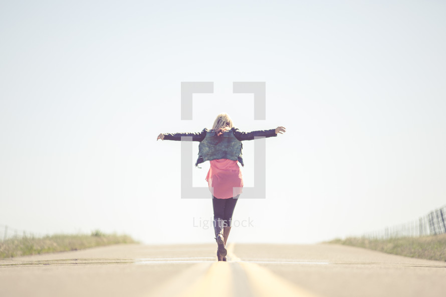 Woman balancing on the stripe in the middle of the road.