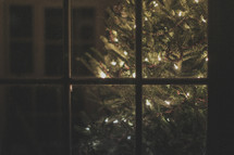 A lighted Christmas tree through a window