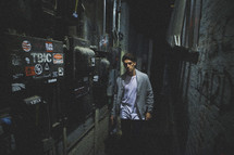 man walking backstage down a dark hallway