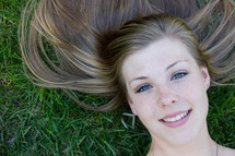 teen girl lying in the grass
