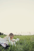 young woman reading on a blanket in the grass
